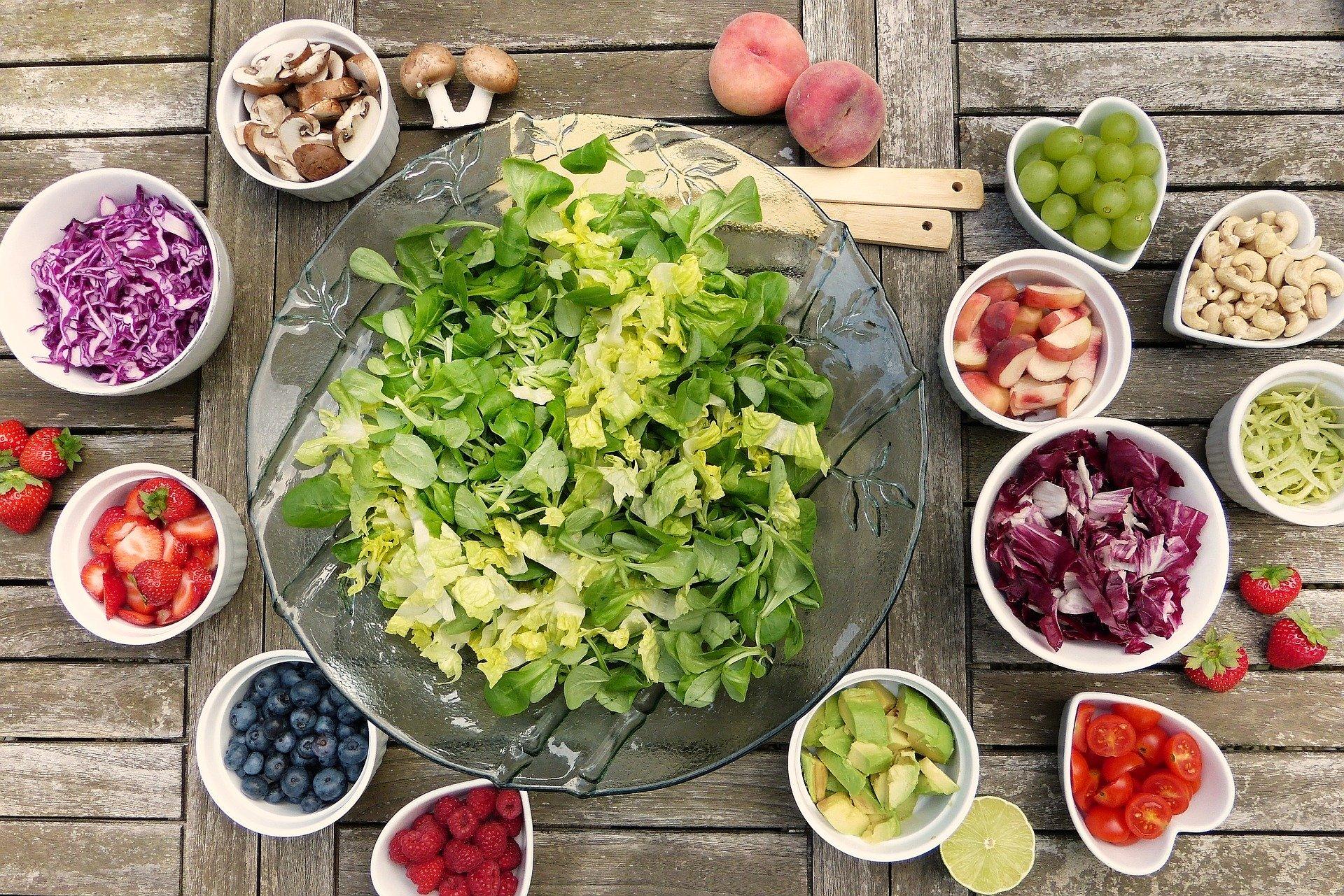 In der Bildmitte ist eine große Salatschüssel zu sehen. Um die Salatschüssel stehen viele kleinere Schüsseln mit geschnittenem Gemüse, Pilzen und Obst.
